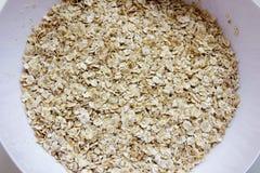 Cereal seco de la avena en una placa blanca foto de archivo