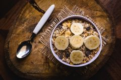 Bowl of cereal with fruit, pieces of banana with oats and cereal. Cereal, seeds and oats, and banana slices, a healthy meal for breakfast or afternoon snack royalty free stock photos