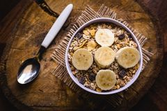 Bowl of cereal with fruit, pieces of banana with oats and cereal. Cereal, seeds and oats, and banana slices, a healthy meal for breakfast or afternoon snack royalty free stock images