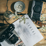 Cereal Travel and Style Magazine With Black Dslr Camera Royalty Free Stock Photos