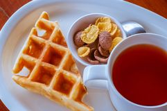 Cereal and waffle placed next to a tea cup Royalty Free Stock Images