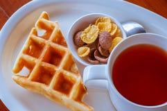 Cereal y galleta colocados al lado de una taza de té Imágenes de archivo libres de regalías