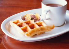 Cereal y galleta colocados al lado de una taza de té Imagenes de archivo