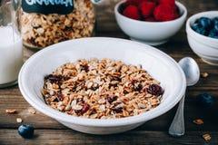 Cereale casalingo del granola con l'avena ed i mirtilli rossi matti ed asciutti Prima colazione sana con latte e le bacche immagini stock libere da diritti
