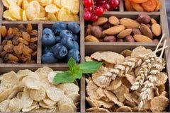 Cereale da prima colazione, frutta secca, bacche e dadi in una scatola di legno Fotografia Stock