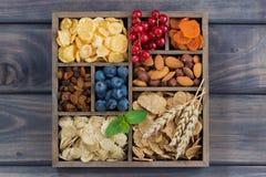 Cereale da prima colazione, frutta secca, bacche e dadi in una scatola di legno Immagine Stock