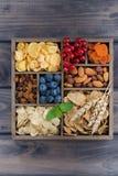 Cereale da prima colazione, frutta secca, bacche e dadi in una scatola di legno Immagini Stock Libere da Diritti