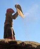 Cereale di pulizia della donna del Nepal con il metodo primitivo Fotografia Stock