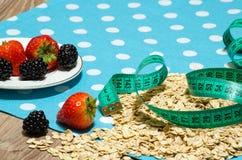 Cereale, fragole, more e nastro di misurazione sulla tavola Fotografie Stock