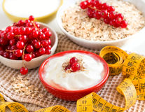 Cereales con las pasas rojas, el yogur y la cinta métrica Imagenes de archivo
