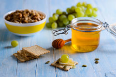 Cereales de desayuno con las uvas, la miel y el muesli en un fondo azul fotos de archivo