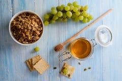 Cereales de desayuno con las uvas, la miel y el muesli en un fondo azul fotografía de archivo