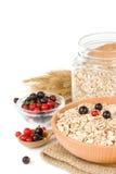Cereales de la escama de la avena en placa con la cuchara en blanco Imagen de archivo