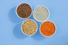Cereales diferentes clasificados en un fondo azul Alforf?n, lentejas, arroz, guisantes en la opini?n superior de las placas fotos de archivo