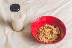 Cereales en cuenco rojo con leche Imágenes de archivo libres de regalías