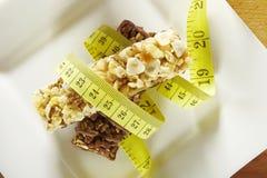 Cereales y barras de chocolate con la cinta métrica en un plato Imagen de archivo