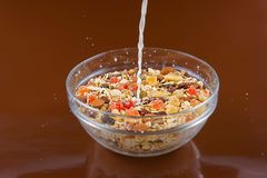 Cereali da prima colazione, farina d'avena con i frutti canditi e dadi in una ciotola di vetro ed in un latte di versamento, fond Fotografie Stock