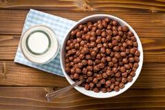 Cereali del cioccolato in ciotola e latte in barattolo Fotografia Stock Libera da Diritti