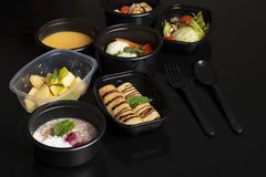 Cereali e bacche, minestra della zucca con le verdure cotte a vapore, lattuga e macedonia di frutta esotica sulla tavola nera fotografie stock libere da diritti