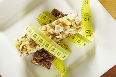 Cereali e barre di cioccolato con nastro adesivo di misurazione in un piatto Immagine Stock