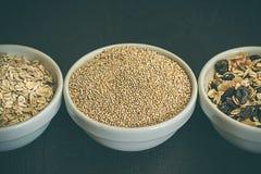 Cereali sani della quinoa, riso sbramato e farina d'avena in una ciotola Concetto dei carboidrati sani immagini stock libere da diritti