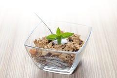 Cereali in una ciotola con yogurt, la menta e la frutta fresca Fotografia Stock