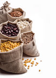Cereals in bags on white. Beans, peas, lentils, rice in canvas bags Stock Photos