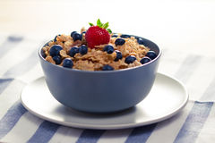 Cereals with berries in a bowl. Cereals with strawberries and blueberries in a bowl Royalty Free Stock Photos
