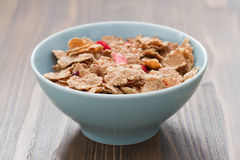 Cereals in blue bowl on brown background Royalty Free Stock Image