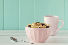 Cereals breakfast. Cereals in a pink bowl on a white wooden table with a robin egg blue background. Vintage style Royalty Free Stock Photos