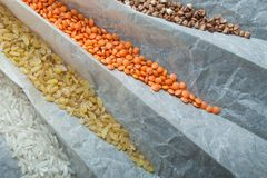Cereals for dietary nutrition on paper, close-up. Rice, bulgur, buckwheat and lentils royalty free stock photo