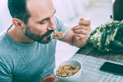 Handsome attractive man having breakfast in the kitchen royalty free stock images
