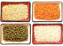 Cereals and legumes. Four little dishes, each one full of two types of rice (moti and carolina gold), red lentils and  green-mung  beans on a white background Royalty Free Stock Images