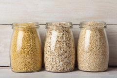 Cereals. Various cereals in glass jars  on wooden background Royalty Free Stock Photography