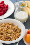 Cereals in white bowl with milk and fruits. On blue wooden background Royalty Free Stock Images