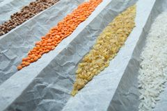 Cereals in wrapping paper, close-up. Rice, bulgur, buckwheat and lentils royalty free stock images