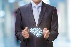 Cerebros en las manos del hombre de negocios Foto de archivo libre de regalías
