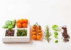 Cereja alaranjada orgânica do êxtase com manjericão e pimenta e alecrins na caixa de madeira branca no fundo de pedra da cozinha  fotografia de stock royalty free