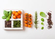 Cereja alaranjada orgânica do êxtase com manjericão e pimenta e alecrins na caixa de madeira branca no fundo de pedra da cozinha  foto de stock