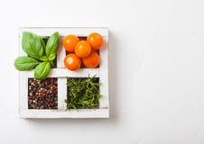 Cereja alaranjada orgânica do êxtase com manjericão e pimenta e alecrins na caixa de madeira branca no fundo de pedra da cozinha  imagens de stock royalty free