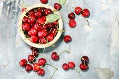 Cereja Cerejas frescas vermelhas na bacia e um grupo das cerejas no th imagem de stock