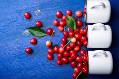 Cereja dispersada dos copos do esmalte Cerejas no copo do ferro no fundo de madeira azul Saudável, fruto do verão Cerejas três a  Imagem de Stock