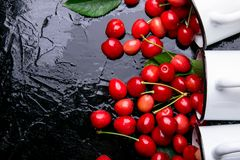 Cereja dispersada dos copos do esmalte Cerejas no copo do ferro no fundo preto Saudável, fruto do verão Cerejas três Vista superi Imagens de Stock