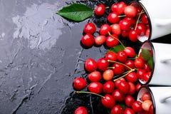 Cereja dispersada dos copos do esmalte Cerejas no copo do ferro no fundo preto Saudável, fruto do verão Cerejas três Vista superi Fotos de Stock