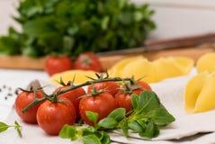 Cereja do tomate, massa, sal, vegetariano italiano da especiaria do ingrediente da manjericão preta do fundo fotografia de stock