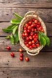 Cereja Cereja doce fresca com as folhas na cesta na tabela de madeira fotografia de stock royalty free