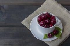 Cereja doce madura orgânica fresca em uma caneca cerâmica branca imagem de stock royalty free
