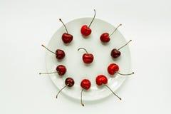 A cereja doce vermelha encontra-se em uma placa branca, um isolador imagem de stock royalty free