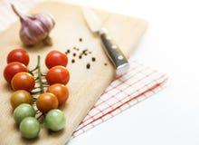 Cereja dos tomates com alho e pimenta preta na placa de madeira Graus diferentes de madureza da cereja dos tomates Foto de Stock Royalty Free