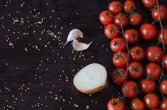 Cereja dos tomates com metade da cebola e do alho no lado Fotografia de Stock